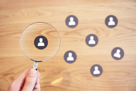 Human resources management and recruitment concept, Hand holding magnifying glass search people paper icon on top desk.
