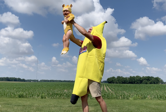 Tennessee dad Hans Schlegel raises his 1-year-old son, Stein, into the air like Simba the lion cub during a shoot for his family's music video. The Schlegel family entered a contest sponsored by DOLE food and inspired by Disney's The Lion King that asked people to share family traditions. They took it to the extreme with a banana suit, a lion costume, a fun rap and a video starring their two kids and three dogs.