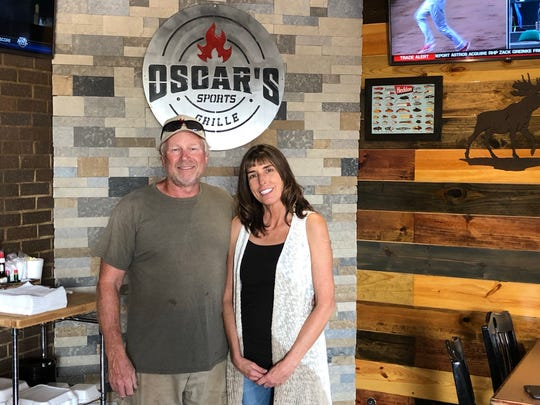Sherri and Barry Smith are pictured in front of the fireplace in the outdoor patio at Oscar's Sports Grille in Gallatin.