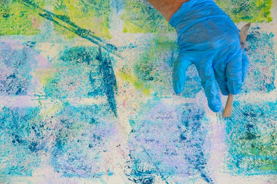 Madeline Sugerman applies texture to a new painting in her Empathic series at Naples Art Association on Thursday, August 1, 2019, in Naples.
