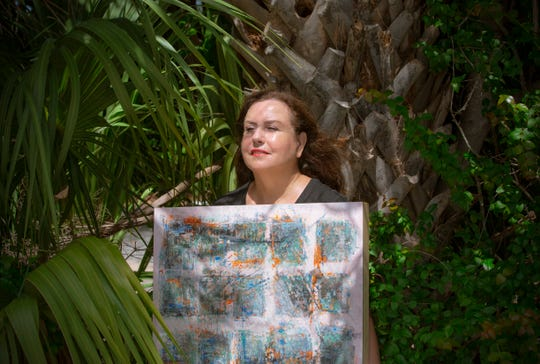 Madeline Sugerman poses for a portrait holding her Empathic II at Naples Art Association on Thursday, August 1, 2019, in Naples. Madeline is an artist who uses two mediums, encaustic and cold wax, in her painting, to enhance the perception and magnificence of nature.