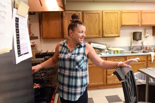 "Certified Peer Supporter Tara Midkiff greets a client while frying up some bacon during a ""cooking with Tara"" class on Wednesday evening at the Main Place in Newark. Midkiff started as a housekeeper at the local non-profit before moving into her current roll as well as working with the Quick Response Team for Opiate Overdoses in Newark."