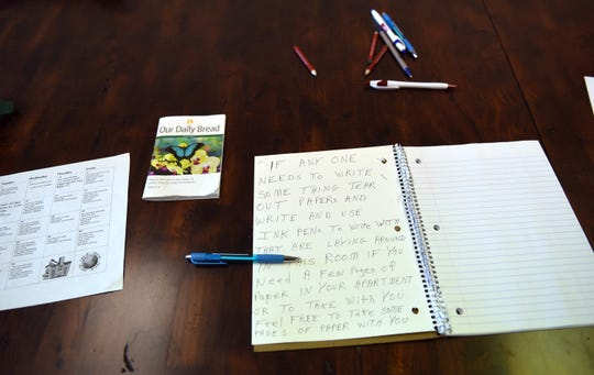 Writing materials left out by a resident in a common area for neighbors at The Main Place's housing behind its South Third Street location.