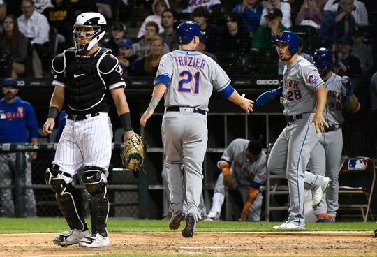 New York Mets' Todd Frazier (21) celebrates with J.D. Davis (28) after Frazier scored during the ninth inning of the team's game against the Chicago White Sox on Wednesday, July 31, 2019, in Chicago. White Sox catcher James McCann is at left.