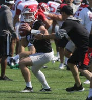 Rutgers quarterbacks, Cole Snyder tries to not let the ball get knocked out of his hands during a passing drill during Rutgers football practice this morning at their facility in Piscataway on August 1, 2019.