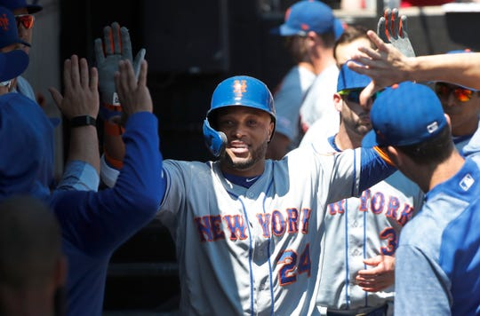 New York Mets' Robinson Cano celebrates his home run off Chicago White Sox starting pitcher Dylan Cease, in the dugout during the second inning of a game Thursday, Aug. 1, 2019, in Chicago.