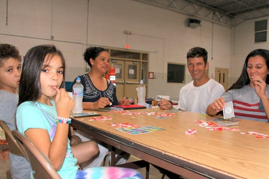 Family members and staff enjoy a game of Loteria at the Deming Migrant Relief Shelter.