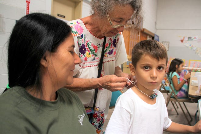 From left, A Brazilian mother and her son fashion hand-crafted jewelry from beads.