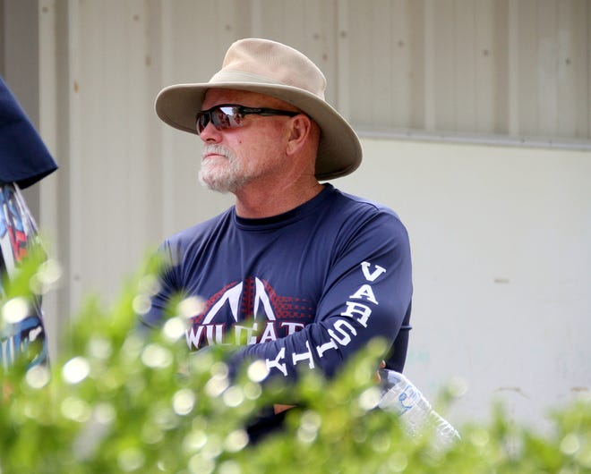 Deming High football coach Greg Simmons looks out onto an off-season workout.