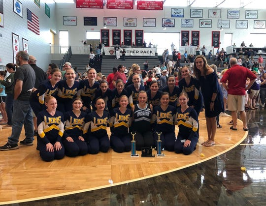 The South Lyon JV pom team poses with their trophies.