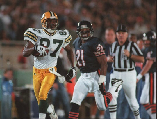 1995 SEASON: Green Bay Packers' Robert Brooks (87) takes a reception 99 yards for a touchdown as the Chicago Bears' Donnell Woolford (21) looks on during the second quarter in Chicago on Sept. 11, 1995.