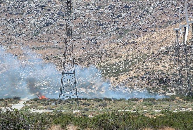 A small brush fire burns near wind turbines near Haugen-Lehmann Way just west of Palm Springs, August 1, 2019