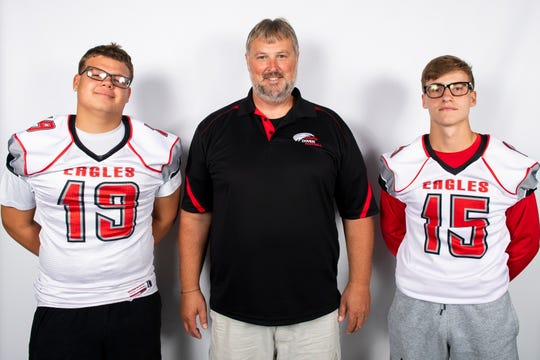 Dover football players Justin Johnson (19) and Cam Fetrow (15) pose for a photo with head coach Wayne Snelbaker during YAIAA football media day in Hanover on Thursday, August 1, 2019.