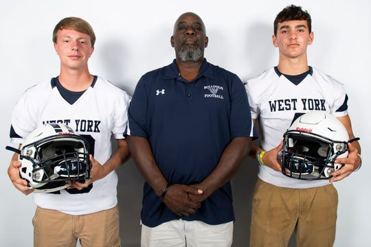 West York football players Corey Wise, left, and Joey Dejesus pose for a photo with assistant coach Cornell Parker during YAIAA football media day in Hanover on Thursday, August 1, 2019.