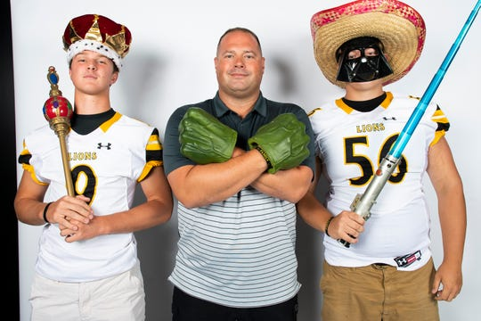 Red Lion football players Nic Shultz (9) and Jared Miller (56) strike a pose with head coach Jesse Shay during YAIAA football media day in Hanover on Thursday, August 1, 2019.