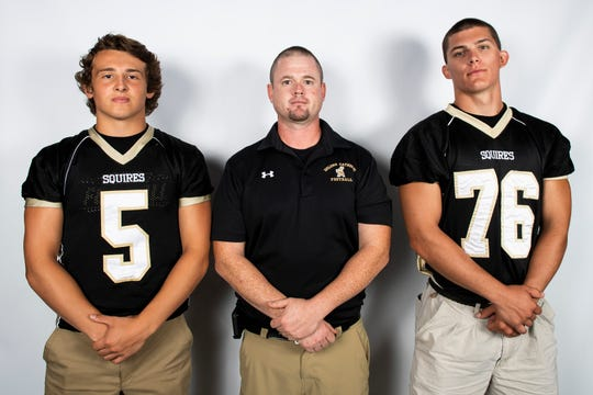 Delone Catholic football players Kevin Mowrey (5) and Austin Staub (76) pose for a photo with head coach Corey Zortman during YAIAA football media day in Hanover on Thursday, August 1, 2019.