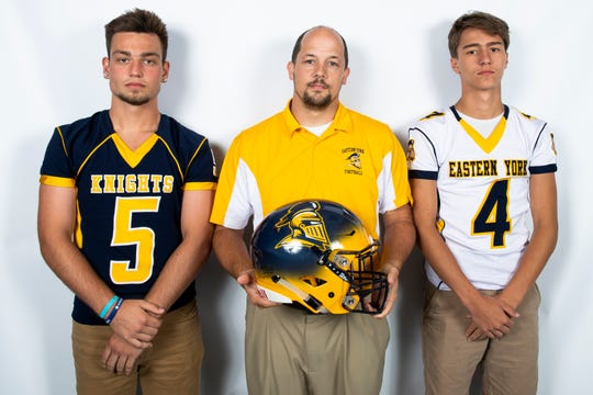 Eastern York football players Kaleb Corwell (5) and Trevor Seitz (4) pose for a photo with head coach Josh Campbell during YAIAA football media day in Hanover on Thursday, August 1, 2019.