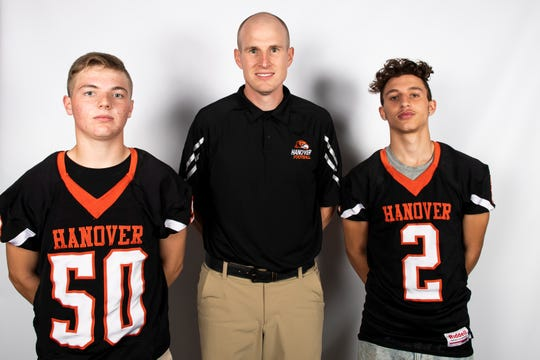 Hanover football players Aaron Eisenhart (50) and Andrew Caban (2) pose for a photo with head coach Brandon Bishop during YAIAA football media day in Hanover on Thursday, August 1, 2019.