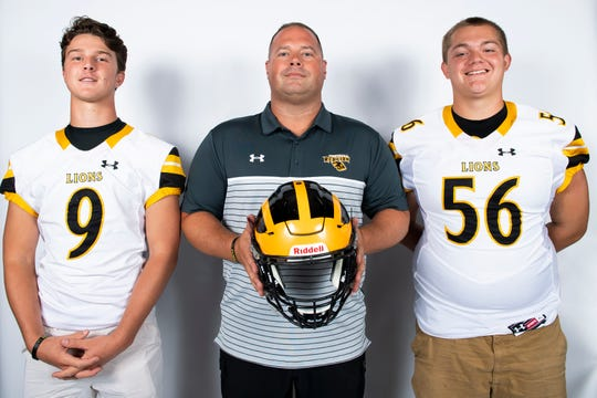 Red Lion football players Nic Shultz (9) and Jared Miller (56) pose for a photo with head coach Jesse Shay during YAIAA football media day in Hanover on Thursday, August 1, 2019.