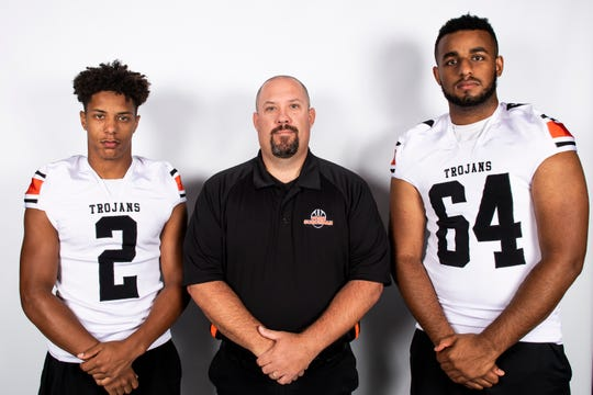 York Suburban football players Savion Harrison (2) and Devante Banks (64) pose for a photo with head coach Andy Loucks during YAIAA football media day in Hanover on Thursday, August 1, 2019.