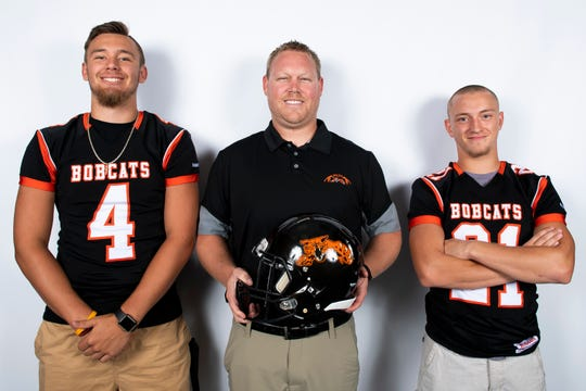 Northeastern football players Zech Sanderson (4) and Austyn Hays (21) pose for a photo with head coach Jon Scepanski during YAIAA football media day in Hanover on Thursday, August 1, 2019.