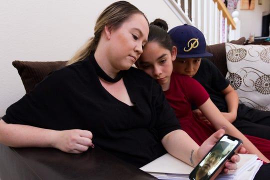 La estadounidense Christine Palomar (i) habla a través de un teléfono junto a sus hijos Joshua (c) y April (d), el 31 de julio de 2019, con su esposo, el mexicano José Palomar.