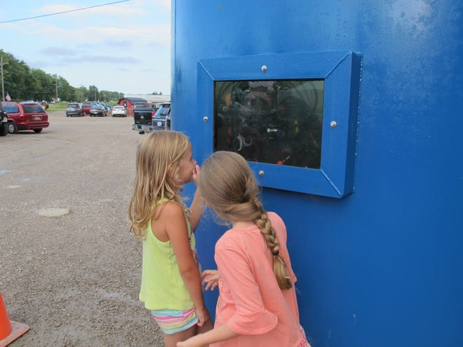 Children look at a diver inside a tank during Tuesday's fundraiser for the St. Clair County Dive Team.