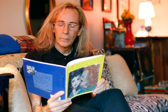 """Mark Dema browses a copy of his book """"Poetry Transcends Time"""" at his home in Fishkill on July 31, 2019."""