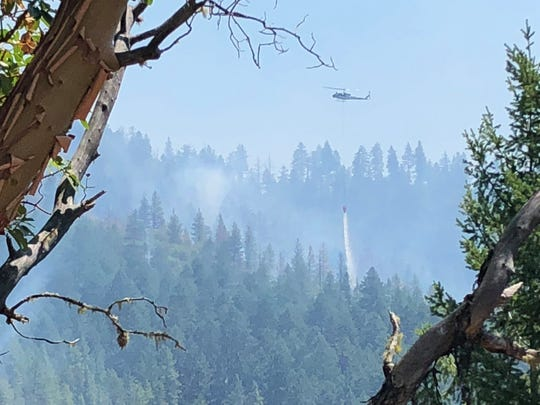 A helicopter drops water over the Panther Gulch Fire burning in southwest Oregon on Wednesday.