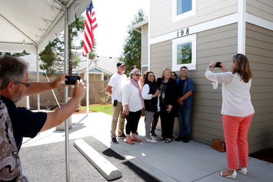 Members of the Polk County Community Development Corporation get their photo taken during a celebration of Operation Welcome Home outside a new veterans housing complex in Independence, Oregon, on Wednesday, July 31, 2019.