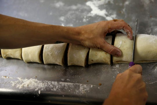 Amanda Nelson cuts cinnamon roll dough into pieces at Jefferson Bakehouse in Jefferson, Oregon,  July 31, 2019.