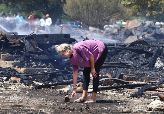 Hope Hoelscher, 19, looks over remains Monday, July 29, 2019, of the Church of the Visitation in Westphalia, Texas. The historic church founded in 1883 burned to the ground in an early morning fire. The cause of the fire is unknown. ( Jerry Larson/Waco Tribune Herald via AP)