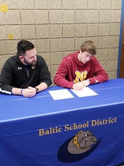 Sam Muston (right) signs his letter of intent to play at Northern State beginning this fall.
