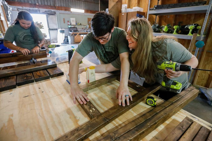 Heather Dyer, right, reaches underneath Brittany Dyer to get a screw while assembling a barstool along with Lainie Vicat, left, at Beautiful Fight Woodworking on Friday, July 26, 2019, in Springfield, Mo.