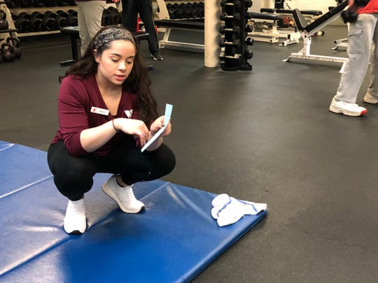 Erika Hernandez guides a client through a set of ab exercises at the Staunton-Augusta YMCA in spring 2019.