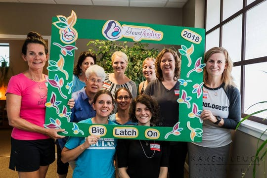 People involved in the 2018 St. Cloud Latch On event pose for a photograph.