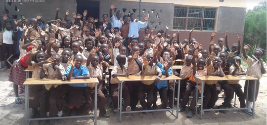 Students in Linvingstone, Zambia sitting in their new desks that were purchased with the help of Necklaces of Love donations.