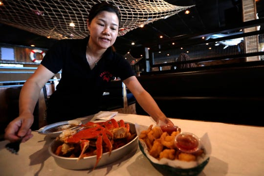 Ivy Lin, owner of the Tallahassee location of Crafty Crab, serves a basket of fried shrimp Thursday, Aug. 1, 2019.