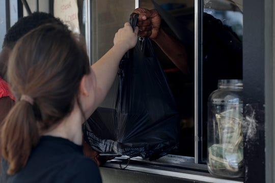A customer picks up their bag of barbecue plates from the window at E&J 5 Buck BBQ on South Monroe Street Saturday, July 27, 2019.