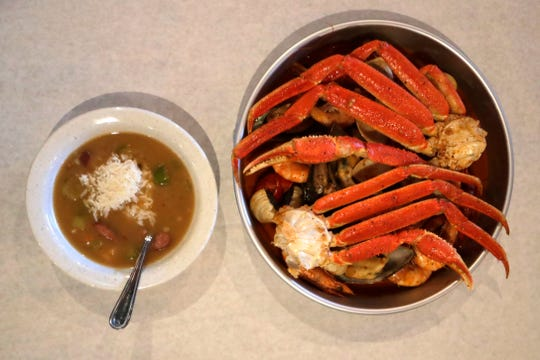 A bowl of gumbo, left, and a small platter of the seafood boil at Crafty Crab.