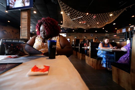 Jocelyn Nelson, left, reads over the menu at Crafty Crab while deciding what she will order for lunch Thursday, Aug. 1, 2019.