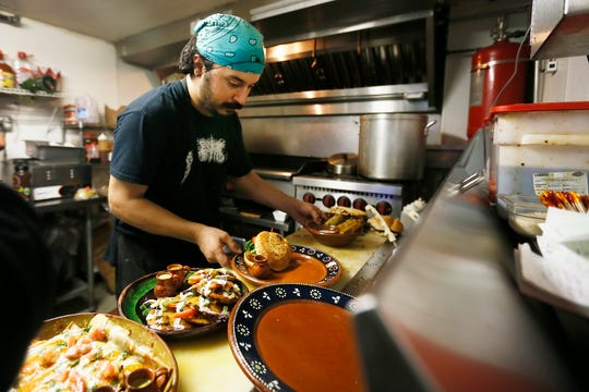 """Lick it Up cook Sam Vasquez gets an order ready at the new location at 114 E. Mills Ave. in Downtown El Paso on Wednesday, July 31, 2019. Vasquez and cook Daniel Rivas (not shown) prepared gorditas, flautas and a buffalo """"chicken"""" sandwich. Lick It Up serves plant-based food and will be featured on """"Diners, Drive-Ins and Dives"""" on Friday, Aug. 2."""