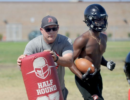 Head coach Jim Bittner goes over some drills with his running backs, including CJ Lewis, during Rio Mesa High's practice on Wednesday.