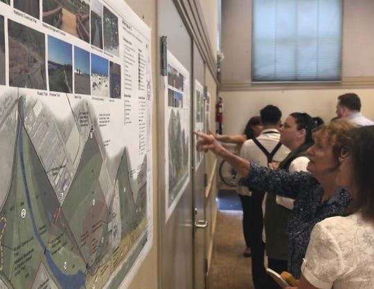 Participants at a meeting on Ormond Beach restoration last week in Oxnard consider the various maps for the project, which could begin construction in 2024.