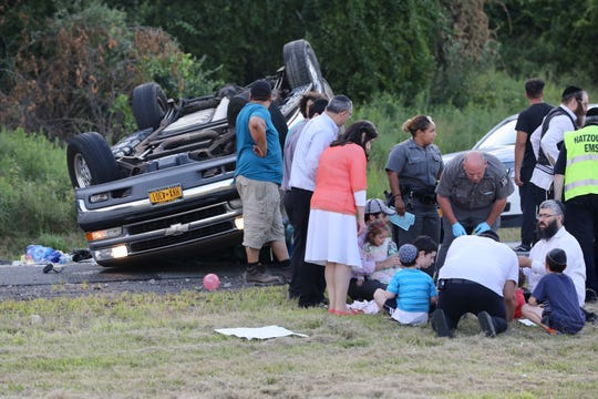State police attend to a woman and several children who were involved in a one-vehicle accident on the Thruway entrance to the Garden State Parkway in Ramapo on Aug. 1, 2019.