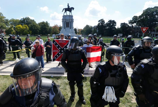 FILE - In this Sept. 16, 2017 file photo, State Police keep a small group of Confederate protesters separated from counter demonstrators in front of the statue of Confederate General Robert E. Lee on Monument Avenue in Richmond, Va. The Confederate statue in Charlottesville, that became a rallying point for white nationalists, was found vandalized Wednesday, July 24, 2019, with an expletive against President Donald Trump. (AP Photo/Steve Helber, File)