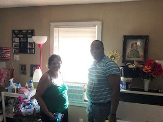 Gwen Yawn, daughter of Beverly Korgere, and Johnnie Williams, New Jerusalem Baptist Church deacon, stand in front of an air-conditioner installed for Korgere as shown in this Aug. 1, 2019, file photo. The church has been helping seniors stay cool nearly 14 years.