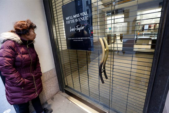 In this Jan. 2, 2019, file photo a woman pauses to read a farewell sign from outside Lord & Taylor's flagship Fifth Avenue store which closed for good in New York.