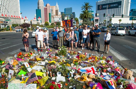 Visitors pay their respects at a memorial in the middle of Las Vegas Boulevard across from the scene of a shooting on Oct. 6, 2017.