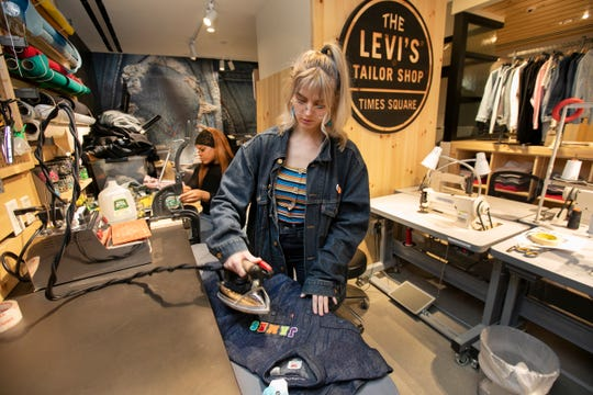 In this June 14, 2019, photo tailors Latoya Henderson, left, and Aly Reinert work in the Levi's Tailor Shop, in the Levi's store, in New York's Times Square.
